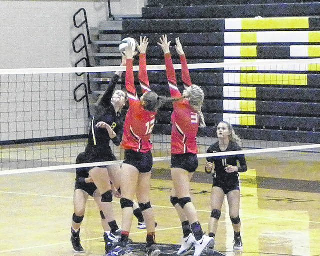 Pettisville's Megan King, left, goes for a kill between Wauseon's Sydney Zirkle (12) and Chelsie Raabe (3). The Indians would sweep the Blackbirds Thursday, 25-21, 25-11, 26-24.