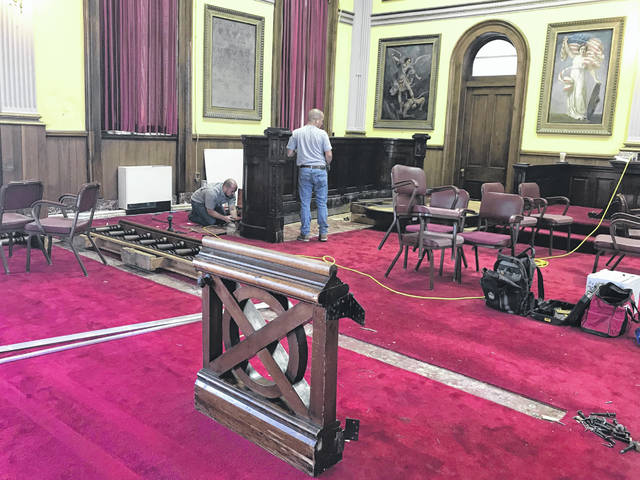 "The last piece of the original ""bar"" stands in the forefront, as crews from Stull Woodworks, Inc. of Troy, Ohio disassemble the jury box in the Historic Common Pleas Courtroom."