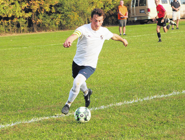 Andrew Hogrefe of Archbold races ahead to keep a ball from going out of play Thursday versus Liberty Center in a game that decided the NWOAL boys soccer title. The Bluestreaks emerged victorious 3-1.