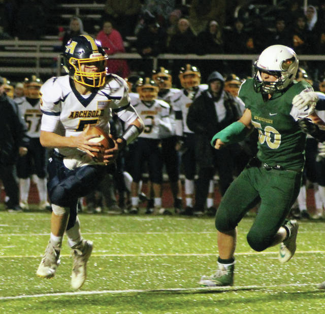 Brandon Taylor of Archbold rolls out and is chased by Evergreen's Isaac Yunker on Friday.