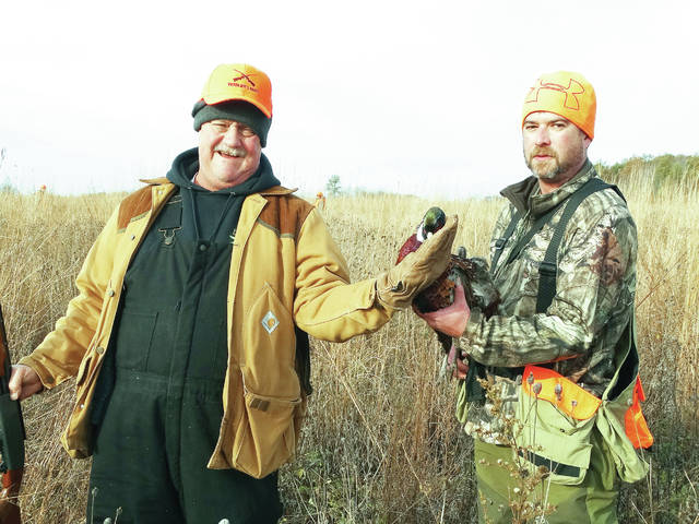 Army veteran Jack Gilsdorf, left, claimed the first pheasant of the day at the 2017 Fulton County Sportsmen Club's Veterans Day Pheasant Hunt. Brian Mitchell, right, Fulton County Chapter of Pheasants Forever, acted as guide and dog handler for the group.