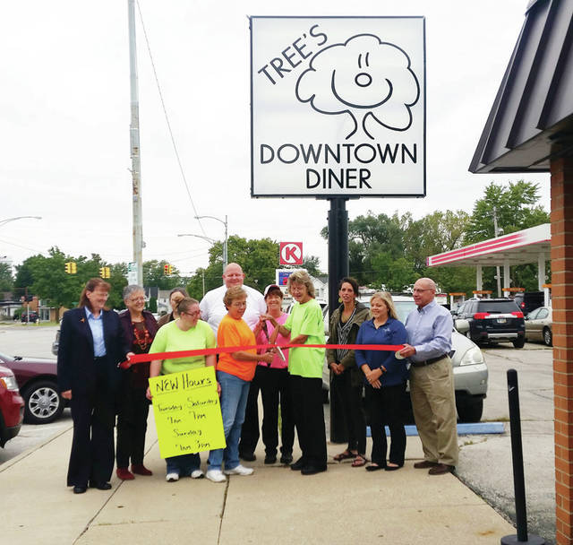 Tree's Downtown Diner owners Dana Aeschliman (center, left) and Teresa (Tree) Spies (center, right) do the honors during a ribbon-cutting ceremony held Sept. 27. The Wauseon restaurant at 224 N. Fulton St. offers daily breakfast, lunch, and dinner specials, and such specialties as biscuits and gravy, half-pound hamburgers, and hand-cut French fries. Tree's is open Tuesday through Saturday, 7 a.m.-7 p.m., Sunday 7 a.m.-3 p.m., and is closed Monday. Also pictured are diner employees and Wauseon Chamber of Commerce members.