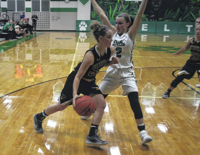 Elizabeth Beck of Pettisville drives the lane as Abby Freeman of Delta defends during Tuesday's game. The Panthers would hold on for a 57-51 win.