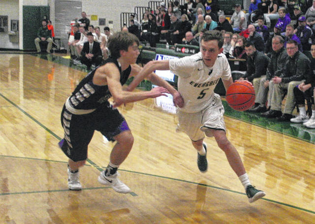 Bryce Hudik of Evergreen, right, drives to the hoop in a game last season. He averaged nearly 11 (10.7) points per game a year ago.