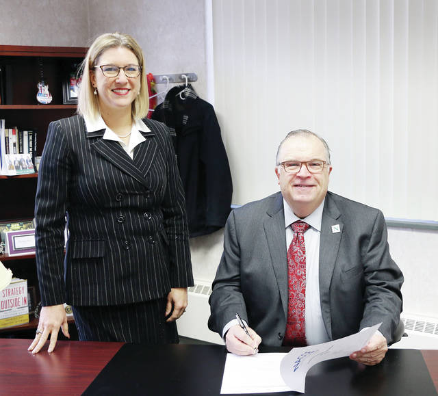 "NSCC President Dr. Michael Thomson signs the ""Presidents for Entrepreneurship Pledge."" He is pictured with NSCC business faculty member Lisa Becher, who is instrumental in Entrepreneurship education, training, and networking opportunities at the college."