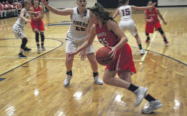 Sydney Zirkle of Wauseon drives along the baseline as Madilyn Hohenberger of Holgate defends Thursday in the opener of the Northwest Signal Holiday Classic in Napoleon. The Indians fell in overtime to the Tigers, 50-48.