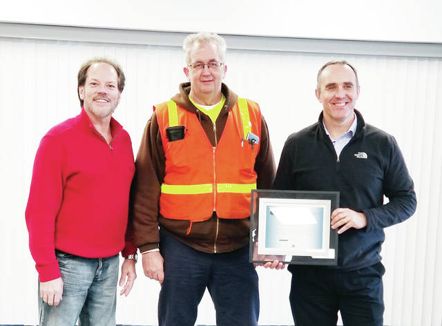 """Dave Rice, center, a North Star Bluescope Steel employee in Delta, is presented a plaque by plant President Robin Davies, right, in recognition of his life-saving CPR efforts on Jeff Wilson, left. Wilson suffered a major cardiac arrest Oct. 9 while playing pickleball with Rice at a park in Holland, Ohio. Rice's immediate efforts likely saved Wilson from death or serious disability, and were featured in an Expositor article Nov. 27 (""""North Star worker helps foil 'widowmaker.'"""") Rice was honored by North Star, which updated his CPR skills with a class about five years ago."""
