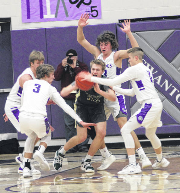Evergreen's Nate Brighton looks for an open teammate as he is surrounded by Bulldogs Friday.