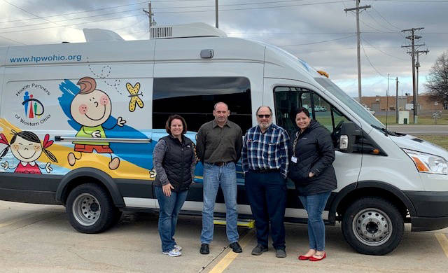 In front of the new mobile dental van are, from left, Tara Brodbeck, registered dental hygienist and van driver; Rob Giesige, ADAMhs Board CEO; Les McCaslin, recently retired ADAMhs Board CEO; and Megan Hall, dental outreach and school based center director.