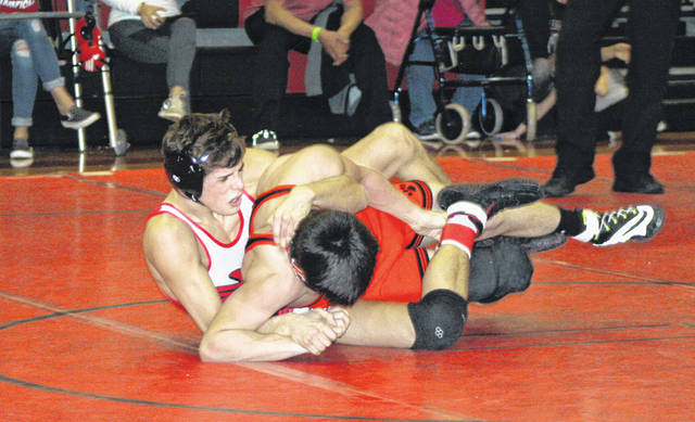 Gavin Ritter of Wauseon, left, puts a hold on Liberty Center's Dylan Matthews during the 120-pound final at Saturday's NWOAL Wrestling Championships. Ritter became a three-time league champion with his 4-2 victory over Matthews.
