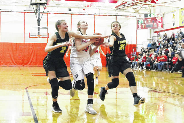 Marisa Seiler of Wauseon, center, heads to the basket through a pair of Evergreen defenders Thursday in NWOAL girls basketball. The Indians nipped the Vikings 32-28.