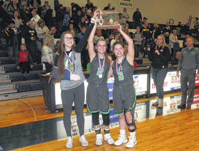 Delta captains Jessie Giguere, Abby Freeman and Alayna Mitchell hoist up the program's first ever district championship trophy following Saturday's win over Woodmore. They defeated the Wildcats 44-29.