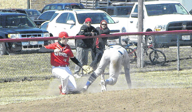 Wauseon third baseman Brady Thomas tags out a Defiance baserunner attempting to steal during the season opener Saturday. A four-run fifth inning for the Bulldogs helped them to a 6-1 win over the Indians.