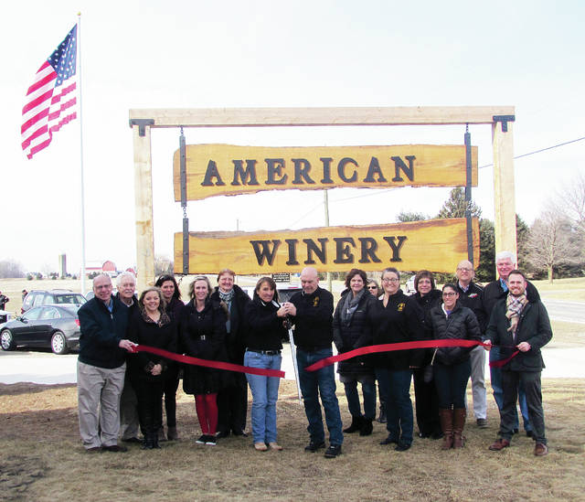 American Winery owners Tom Shank and Connie Simon cut the ribbon during a ceremony Friday marking the grand opening of the new business at 15119 U.S. 20A, just outside of Wauseon. The Fulton County Honor Guard provided the flag in the background. Also attending the ceremony were winery staff members, Chamber of Commerce members, media representatives, and local government officials. The American Winery will be open daily Wednesday through Saturday, noon-9 p.m.