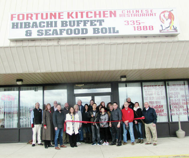 Owner Jenny Lin, right center, and her husband, Zhong Yi Dong, center left, did the honors Friday during a ribbon cutting ceremony for Fortune Kitchen, located at 1487 N. Shoop Ave. in Wauseon. The restaurant was closed for several weeks to add a hibachi grill and a seafood broil. The menu now includes crab, lobster tail, shrimp, mussels, and clams, among other additions. Also pictured are Wauseon Mayor Kathy Huner, members of the city's Chamber of Commerce, and area media representatives.
