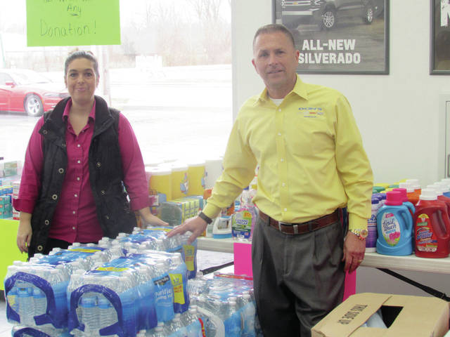 Don's Automotive Group owner Don Hayati and business manager Becky Rhodes display donations received for Midwest flood relief.