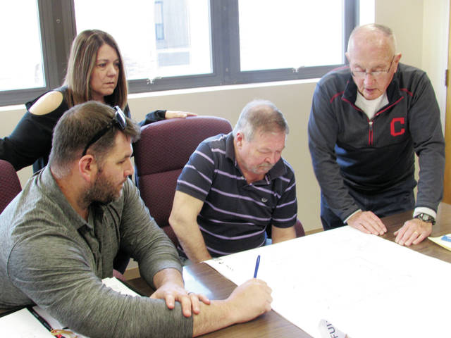 From left, Wauseon Mayor Kathy Huner, Rupp Rosebrock President Justin Groll, and Wauseon Planning Commission members Steve Brown and Larry Fruth review blueprints for an addition to the Fulton County Health Center.