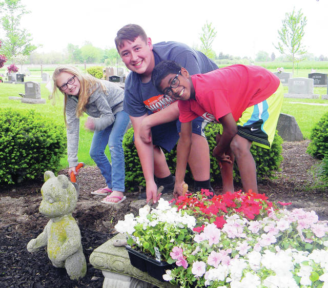 The Green Team 4-H Club braved Sunday's rain and Monday evening's high winds to plant flowers at Wauseon Union Cemetery. It was the club's annual community service project. Pictured, from left, are Matea Burkholder, Tony Vasquez, and Raja Burkholder.