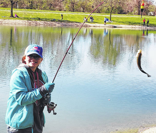 Lauren Valentine of Wauseon shows off her catch during the Wauseon Rotary Fishing Derby on Saturday.