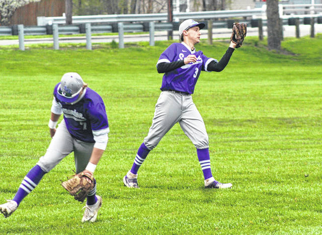 Carter Swank of Swanton makes a catch in left field as shortstop Roman Epley gets out of the way Friday versus Patrick Henry in a NWOAL makeup game. The Bulldogs defeated the Patriots 7-4 both in the league game, and in a five-inning non-league contest.