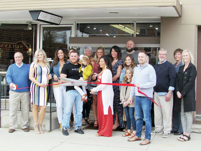 Shawnielle Demaline, owner of Bare Beauty Salon and Spa, 205 N. Fulton St., in Wauseon cuts the ribbon during a grand opening ceremony on Friday. Among the salon's services are styling, coloring, waxing, spray tanning, airbrush makeup and nails. Hours vary. Also pictured are Bare Beauty employees, family members, and Chamber of Commerce members.