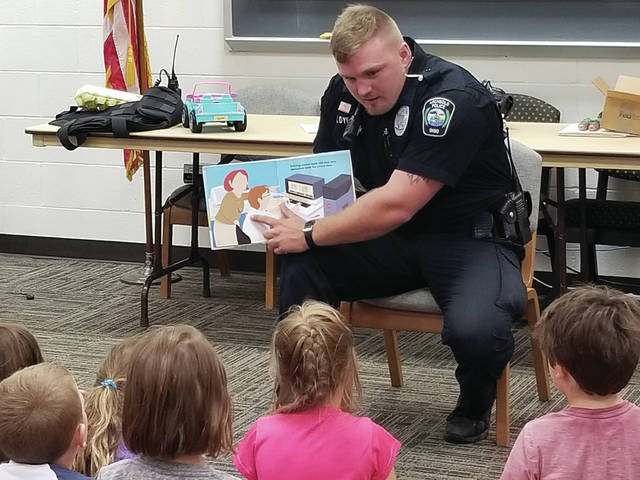 Archbold police officer Xavier Dye teaches children during the village's annual Safety City event being held this week in coordination with the Fulton County Sheriff's Office. Thirty-three children are participating, learning the importance of safety in the home, at school, and on the street. Topics include gun, water, dog, bike, school bus, and fire safety. The children met local police officers, deputies, firefighters and EMS staff, toured the village fire department, met with special educators, and took a bus ride.