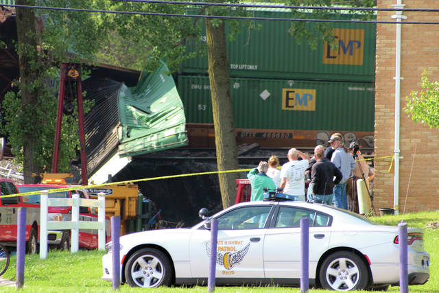 Residents look on Friday morning as work is done to remove the derailed train cars behind the Well Apartments on Dodge Street in Swanton.