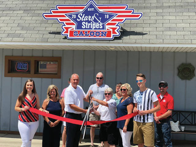 The ribbon is cut during a ceremony Friday at Stars and Stripes Saloon in Lyons.