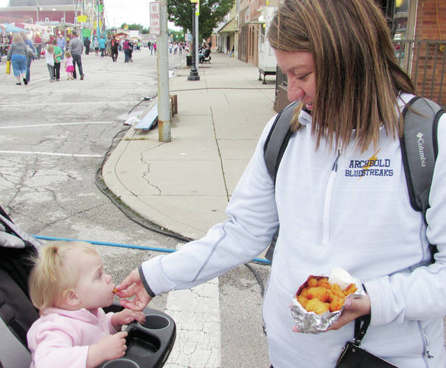 Kate Bernath of Wauseon shares cheese curds with her 18-month-old daughter, Adeline, at Homecoming in downtown Wauseon on Thursday.