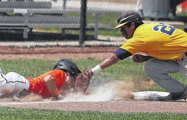 Minster's Eric Schmidt dives safe back into third base as Noah Garcia of Archbold tries to tag him in the bottom of the first inning during the ACME state tournament Sunday.