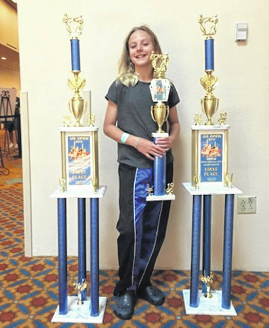Bethani Tibbs of Wauseon stands with her trophies won at the ISKA World Martial Arts Championships held at Coronado Springs Disney World Saturday. She has won a total of 3 ISKA World Championships in the last two years.