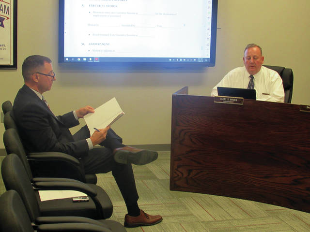 Troy Armstrong, left, incoming Wauseon schools superintendent, traded notes with outgoing superintendent Larry Brown at Monday's school board meeting. Brown has accepted the superintendent's position at Fort Recovery Local Schools in Mercer County, Ohio.