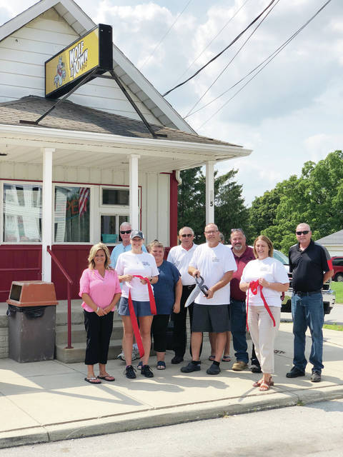 Wes and Beth Wolf led a ribbon-cutting ceremony and grand opening on Friday for Wolf It Down B-B-Q in Lyons. It features meats from the Wolfs' 168-year-old family farm, foods made from scratch, Saturday breakfast, a walk-up window for orders, and a patio area. The restaurant is open Thursday and Friday from 11 a.m.-7 p.m. and Saturday from 6 a.m. – 7 p.m. Meats are also available for purchase. Pictured are Lyons Mayor Andrea Gleckler, Tasha Wolf, Village Council member John Good, Village Administrator Tanya Lumbrezer, Tim Suter, Wes Wolf, Beth Wolf, Julie Fenicle, Township Trustee RJ Lumbrezer, and Village Council member Mark Bryson.