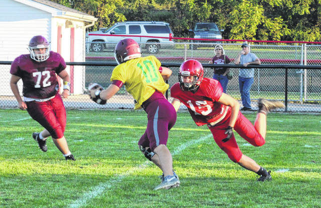 Wauseon's Andrew Figgins, right, puts pressure on Rossford quarterback Kyle Kromenacker during Friday night's Jamboree Game. The Indians open the season on the road at Fairview this Friday.