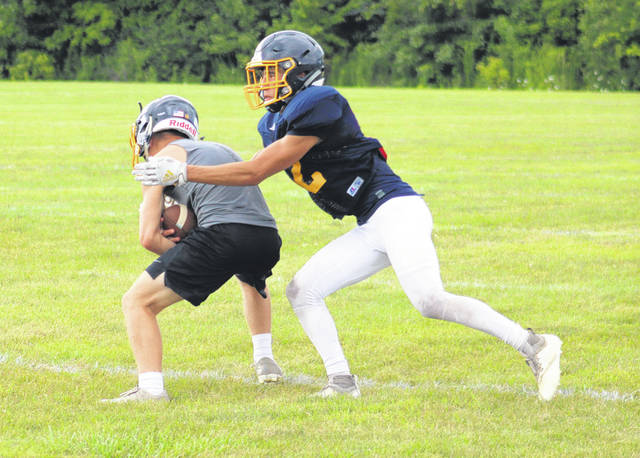 Tony Grime, right, wraps up the receiver as the Archbold defensive backs work on their coverage skills during Tuesday's practice.