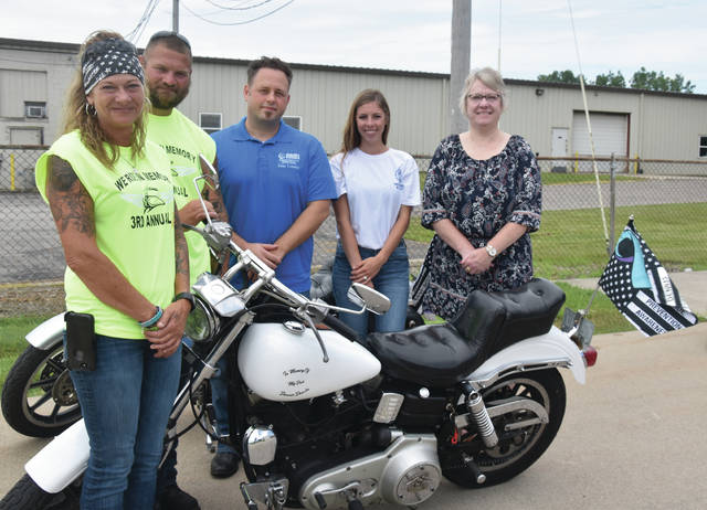 Before the ride in July, Julie Deeds, far left, and her son Justin stand around the 1978 Harley short head cycle that was originally owned by his father, Dennis. Representatives of the three organizations that benefitted from the ride are Rob Spengler, NAMI Four County board member; Mariah Hurst, human resources and benefits administrator for Keller Logistics; and Jenny Hoeffel, manager of Maumee Valley Guidance Center's supportive services for veterans families. Justin rode his father's Harley.