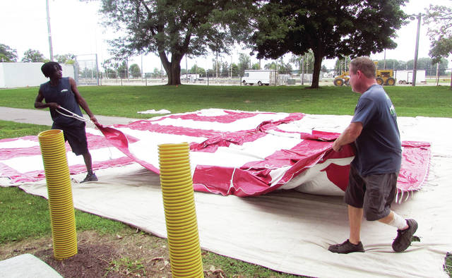 Crew members from Mutton Party and Tent Rental unfold a tent to be raised for the Fulton County Fair.