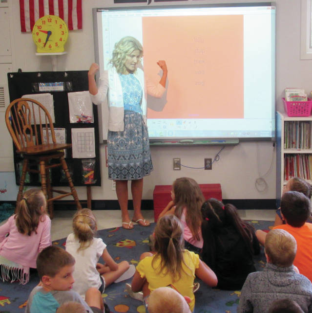 Wauseon Primary School teacher Julie McCaughey demonstrates the strength of words during a lesson Monday morning in her second grade class. It was the first day back to school for the district's students.