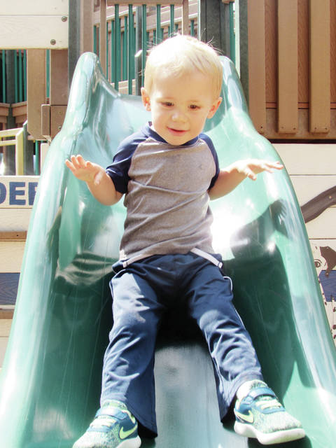 With some encouragement from his mother, Chelsea, two-year-old Grayson Hylander of Fayette takes the plunge on a slide at Imagination Kingdom in Wauseon.