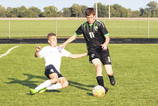 Mike Eckenrode of Delta (11) looks to take the ball upfield as Krayton Kern of Archbold goes for the slide tackle during Tuesday's game. The Blue Streaks shut out the Panthers, 5-0.