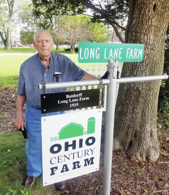 "Long Lane Farm owner Robert Batdorf stands behind the ""Ohio Century Farm"" awarded by the Ohio Department of Agriculture."