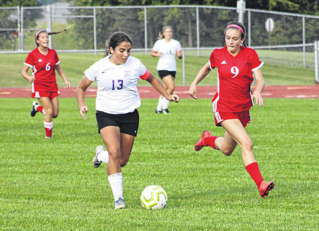 Aricka Lutz of Swanton advances the ball up the field as Eva Mennetti of Wauseon (9) attempts to run her down during Tuesday's NWOAL contest. With seven goals in the game, Lutz reached 50 for her career as the Bulldogs defeated the Indians 9-2.