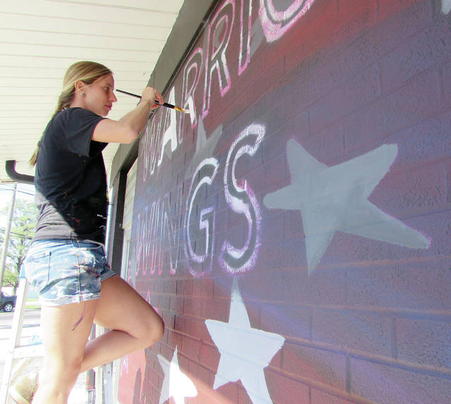 Itinerant artist Erica Arndts finishes a mural in Wauseon commissioned by Wings and Warriors owner Brock Nagel.