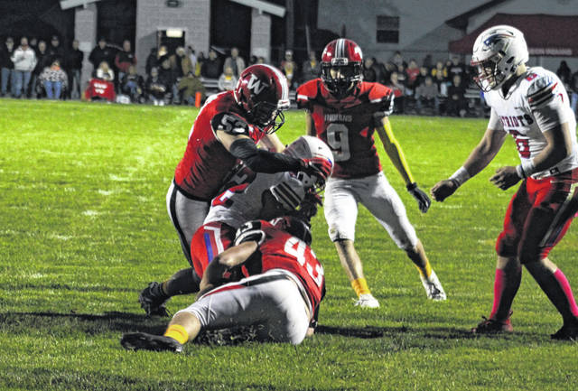Wauseon's Alex Moore, top, along with Isaac Wilson (43) make a tackle on Patrick Henry quarterback TJ Rhamy during Friday's contest. The Indians rallied down 14 points in the fourth quarter, eventually winning in overtime 28-27.