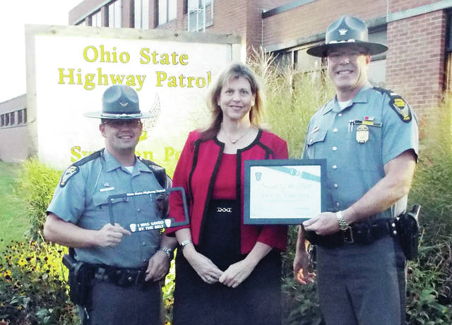 Pictured, from left, is Trooper Tommy Vaculick, Jodi Rabquer, and Lieutenant Vern Fisher.