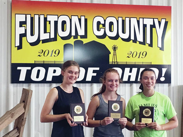 From left, Pettisville FFA members Clara Damman, Kearsten Zuver, and Grace Schnitkey hold their first-place plaques for straw loading at the Fulton County Fair.