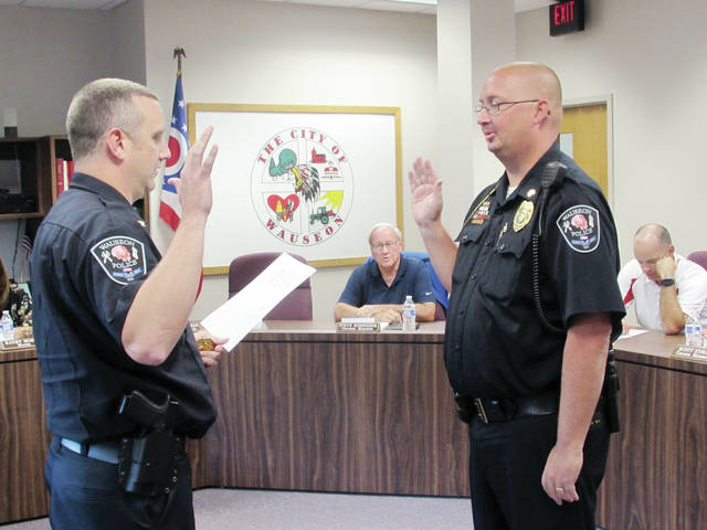 Wauseon Police Chief Kevin Chittenden, left, delivered the oath of office to William Rogers, who was promoted to the rank of lieutenant.