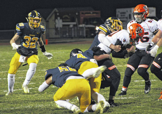 Several Blue Streak defenders corral Coldwater quarterback Jake Hemmelgarn during last week's opening round 27-21 win over the Cavaliers. This week Archbold gets a rematch with Liberty Center, the only team to defeat them in the regular season.