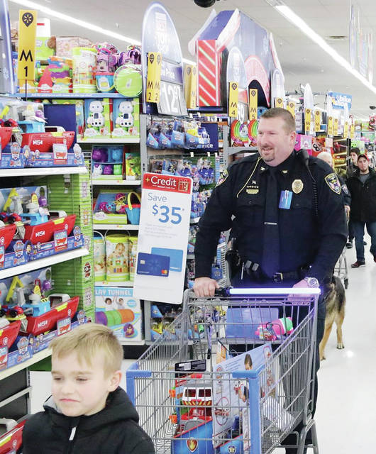 Delta Police Chief Nathan Hartsock helps a youth with his shopping during the 2018 Christmas For Kids in Fulton County event.