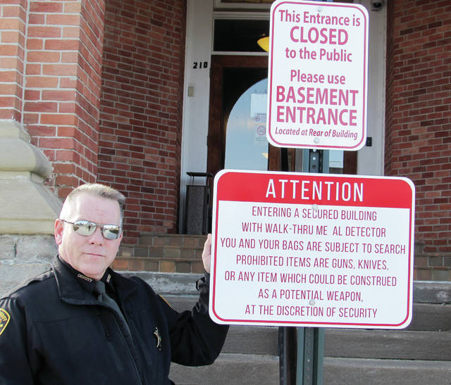 Fulton County Sheriff's Office Sgt. Bryan Coger stands beside a sign installed at the county courthouse entrance in Wauseon.